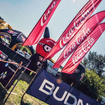 Advertising flags with the CocaCola brand during an automotive event.